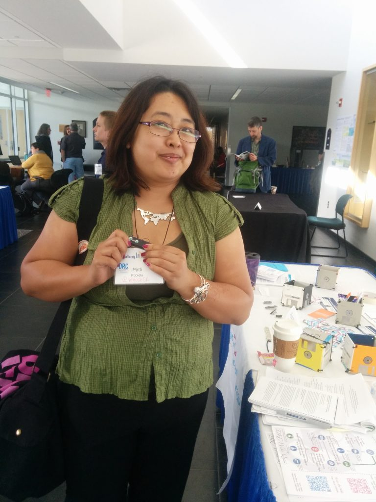 Patti Poblete holds a small computer key with glued on eyes and with a pin backing to wear.