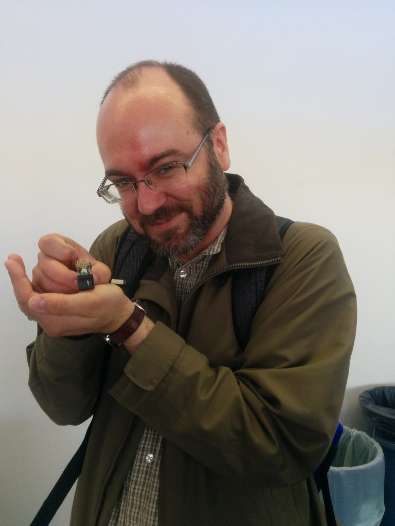 Stedman holds a small computer key with glued on eyes and with a pin backing to wear.