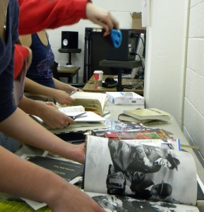 Students cutting up used books at a zine workshop, 2012
