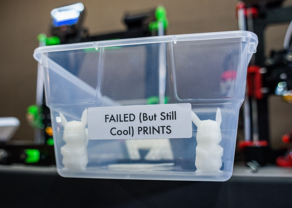 "A clear plastic box with the label ""Failed (but still cool) prints"" contains small 3D printed objects and sits in front of two 3D printers."