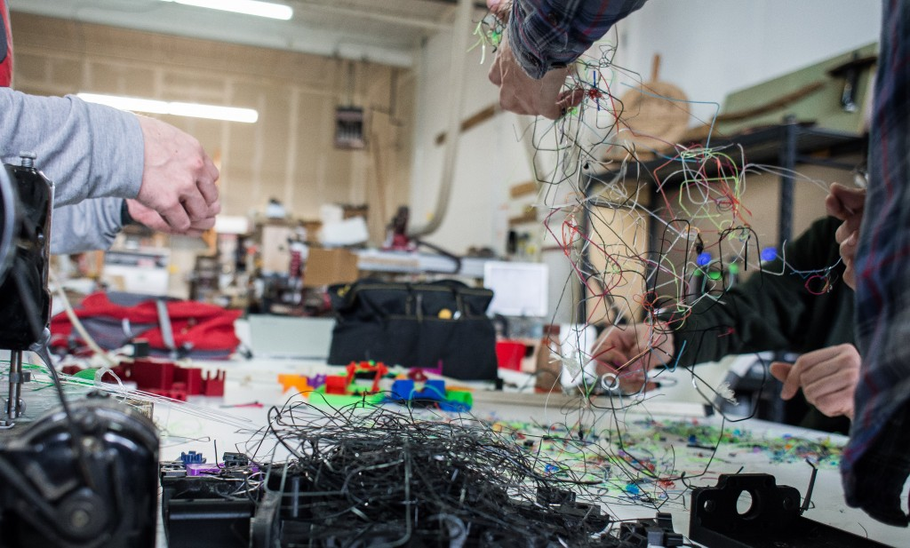 Three sets of hands are pictured sorting through a mass of tangled, multicolored, strands of 3D printer filament.