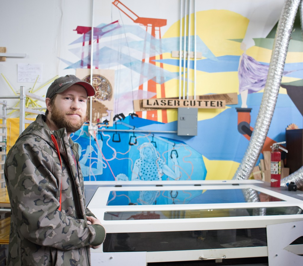 Eric Renn, founder of SoDo MakerSpace, wears a jacket and cap, and he stands in front of a large laser cutter, in front of a wall painted with a multi-colored mural.