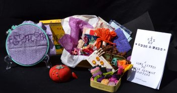 Contents of the kit arranged against a black backdrop including an embroidery hoop, a pincushion, the zine, and a large and small box stuffed with craft materials