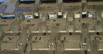 Close shot of keyboard with a clear plastic ergonomic stabilizer