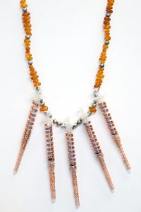 A necklace containing amber beads and syringes.