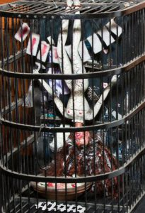 A Barbie doll hangs upside down within a birdcage. The Barbie is mangled and appears her body has taken a toll from the numerous medical procedures that she has been forced to endure.