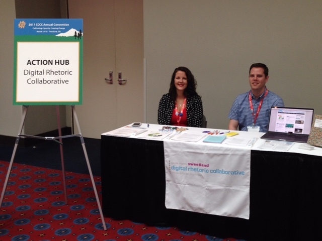 "Two people sit behind a table covered by pamphlets and flyers. On the left is Sara West and on the right is David Coad. To the left of the table, a sign for the Action Hub reads ""Digital Rhetoric Collaborative"""
