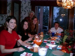 Image of 5 family members around kitchen table making gingerbread houses.