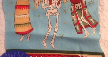 Small piece of fabric illustrating skull figures as angels playing musical instruments