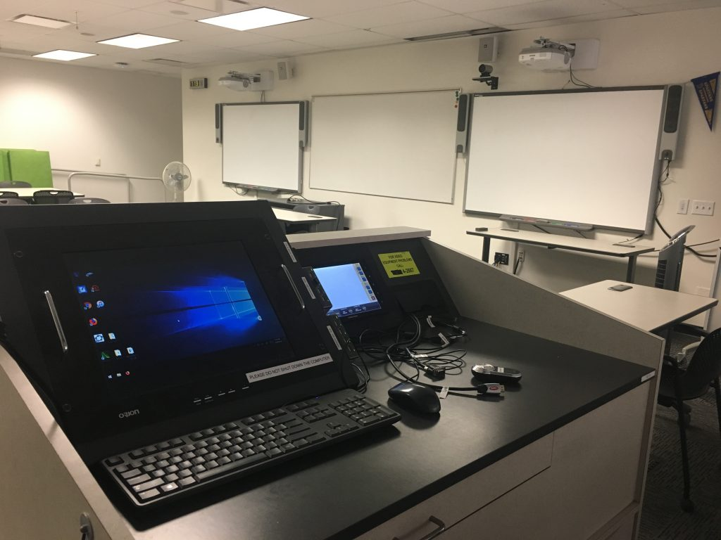 The inside of a Next Generation classroom, featuring a computer, tablet, projection screen, and two smart boards.