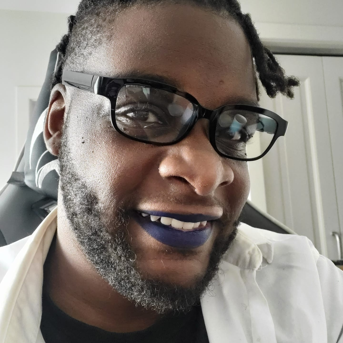 A picture of a black man with a shaved head and dreadlocks wearing glasses, and dark blue lipstick