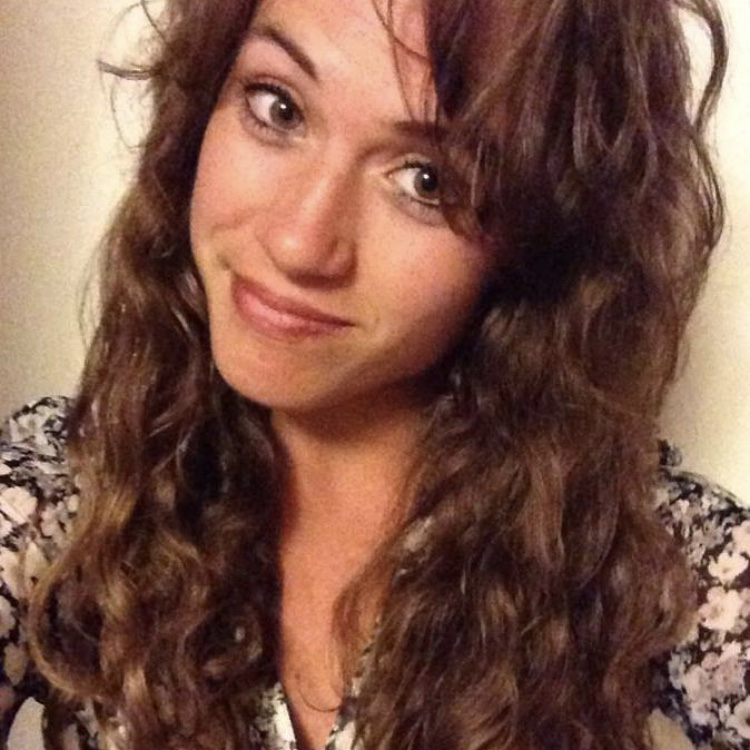 This image shows Danielle, a woman with long and curly brown hair, and a smirk on her face.