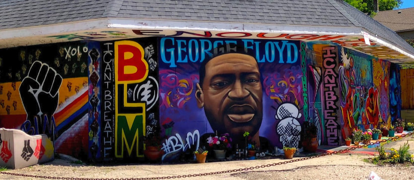 A mural featuring a likeness of George Floyd and Black Lives Matter fist, painted on a building on the corner of North and Holton in Milwaukee, WI.