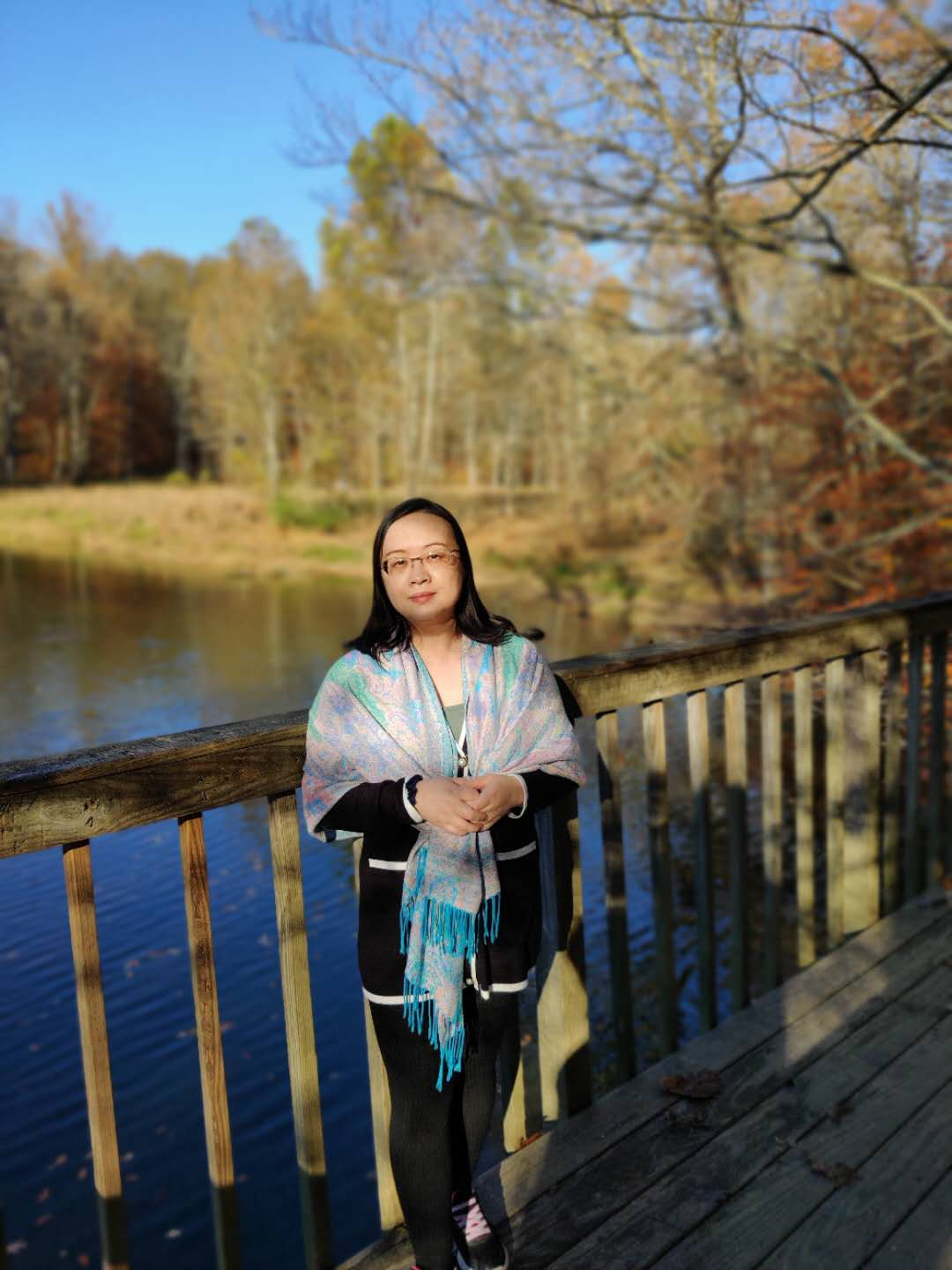 A woman leaning against the rail of a bridge with woods, a lake, and blue sky as the background
