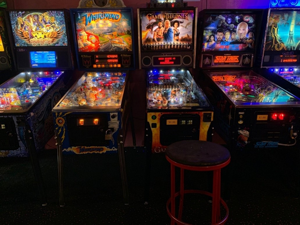 A series of pinball machines lit up in a dark arcade