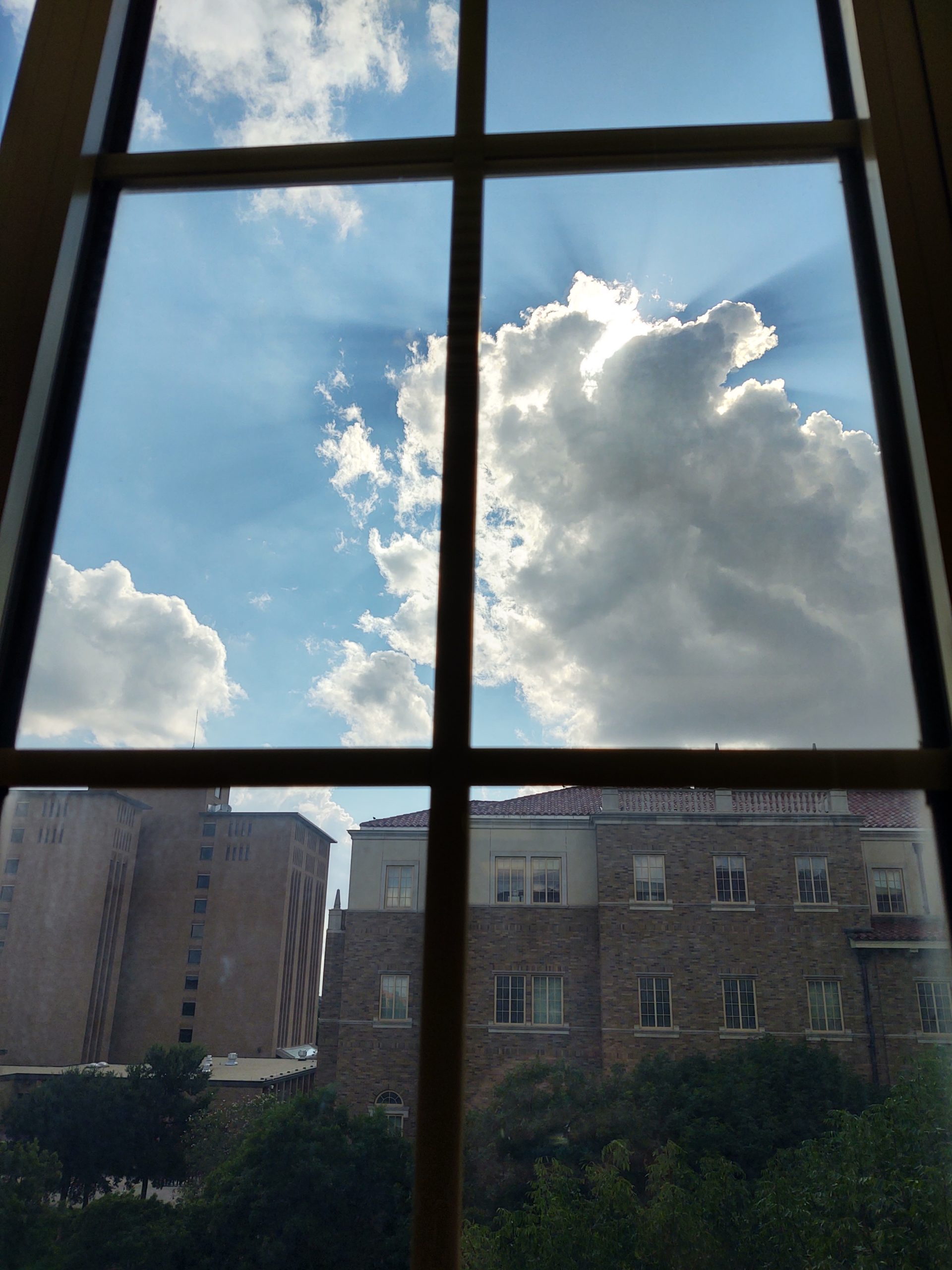 Picture is of sun shining from behind clouds with campus buildings and trees also visible below.