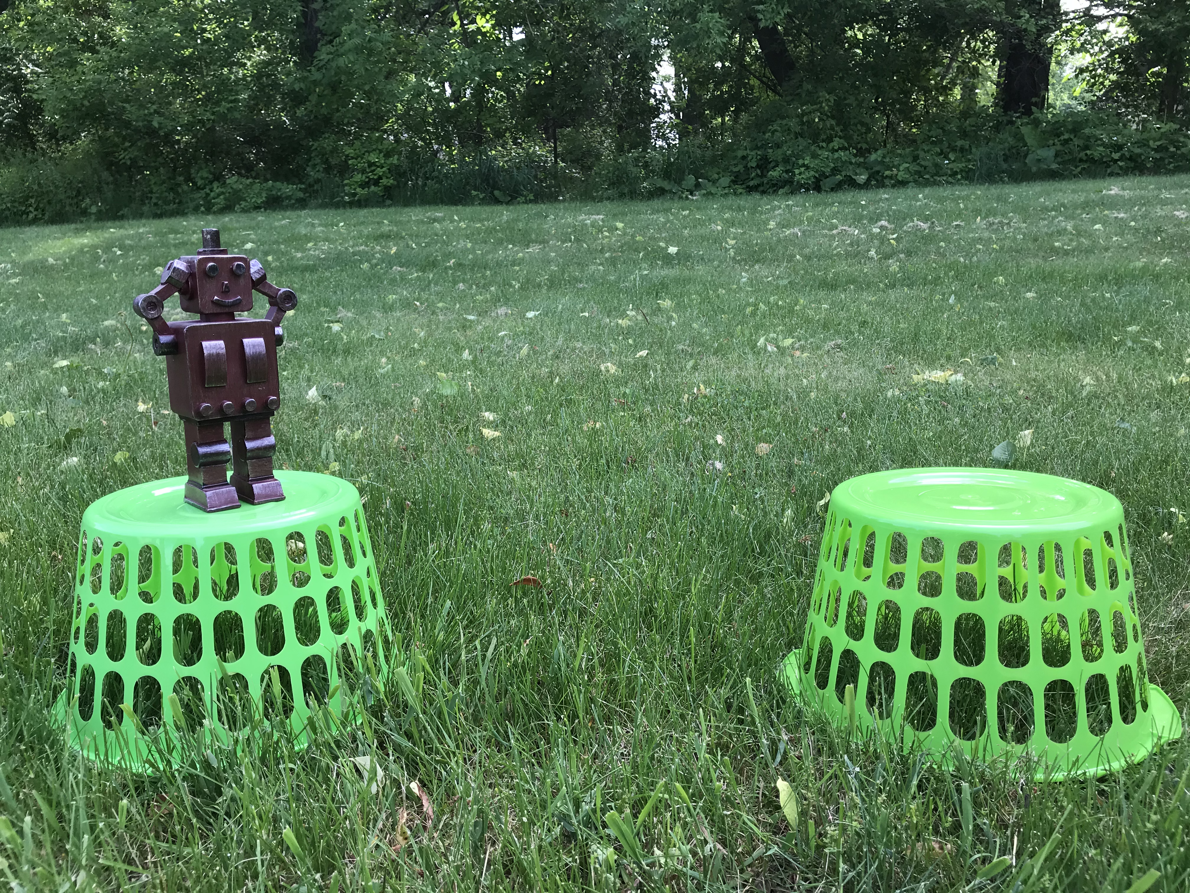 A confused robot toy is pictured on top of an upside-down green basket. Another green basket is about a foot away. Robot's hands are on its head since it cannot cross the gap.